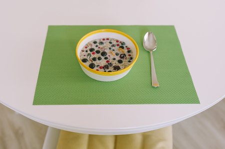 Top view of round table with a bowl of cereals and spoon