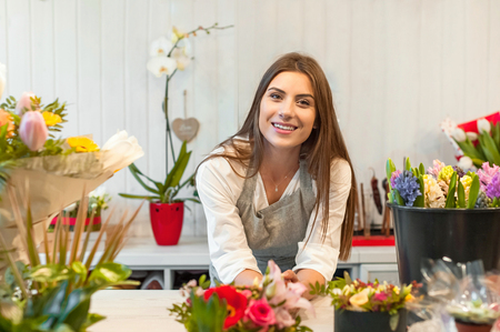 Smiling woman florist small business flower shop owner, at counter, looking frinedly at camera. Zdjęcie Seryjne - 96074979