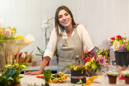 Smiling woman florist small business flower shop owner, at counter, looking friendly at camera.