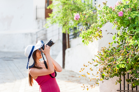 Beautiful young woman tourist with dslr camera taking pictures of beautiful old mediterranean arhitecture and nature in Greece, Europe.