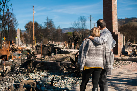 Man and his wife owners, checking burned and ruined of their house and yard after fire, consequences of fire disaster accident. Ruins after fire disaster. Banco de Imagens