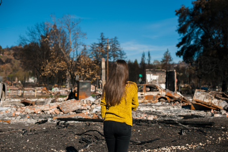Young owner woman checking burned and ruined house and yard after fire, consequences of fire disaster accident. Ruins after fire disaster, loss and despair concept. Stock Photo