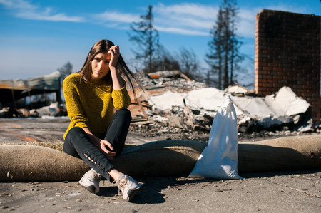 Sad woman home owner holds his head by hand checking burnt out house and yard after fire disaster, consequences of fire disaster accident. Ruins after fire disaster, loss and despair concept. Stock Photo