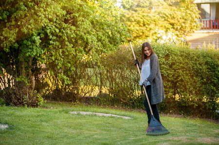 Smiling young woman with garden leaf rake in her home backyard with flowers, plants and vegetation. Gardening as hobby and leisure concept. Stock Photo