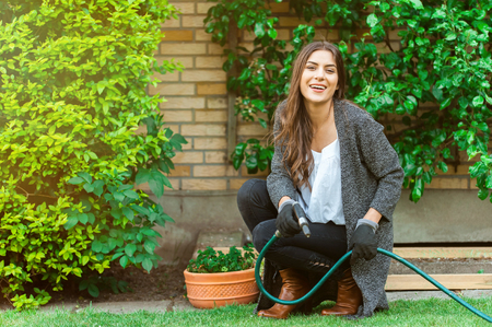 Smiling young woman with garden hose watering her home backyard with flowers, plants and vegetation. Gardening as hobby and leisure concept.