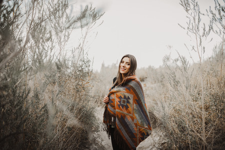 Beautiful hipster traveler girl in gypsy look in desert nature, looking side.  Artistic photo of young hipster traveler girl in gypsy look, in Coachella Valley in a desert valley in Southern California.