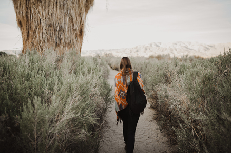 Back side of boho woman in the desert nature with backpack.  Artistic photo of young hipster traveler girl in gypsy look, in Coachella Valley in a desert valley in Southern California.