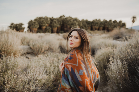 Smiling, pretty hipster traveler girl in gypsy look and windy hair in desert nature.  Artistic photo of young hipster traveler girl in gypsy look, in Coachella Valley in a desert valley in Southern California.