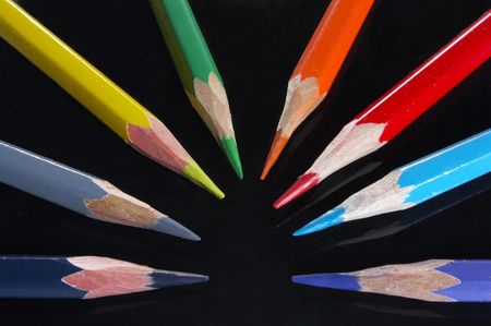 Set of colored pencils on black photo