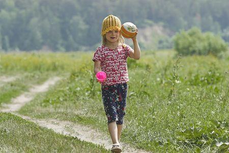 earth road: Poco sorridente ragazza a piedi lungo la strada di terra