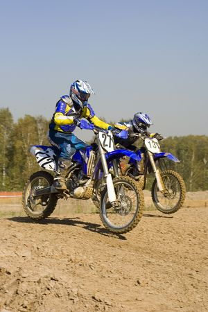 Two motocross riders duelling on their motorcycles