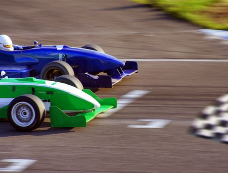 Two formula cars speeding to finish line Stock Photo