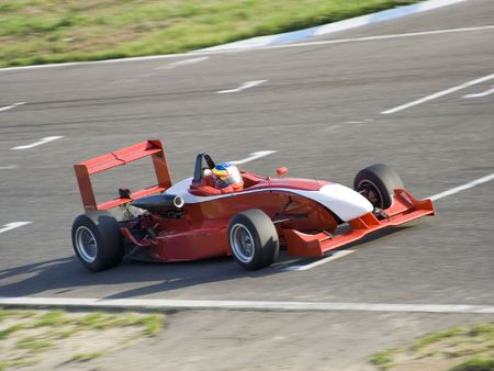 Red racing formula car in a cirquit race