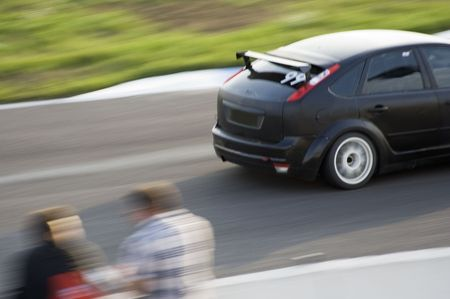 Black sport car moving at high speed along stand
