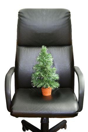 Green christmas tree and black boss's armchair Standard-Bild
