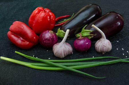 Eggplans, red pepper, onion and garlic on black background Standard-Bild