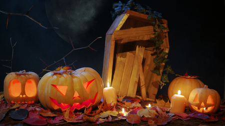 Halloween pumpkin jack o lantern with burning candles on the background of a broken coffin. Moon illuminate an old cemetery. Halloween decorations Stock Photo