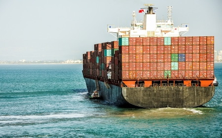 containership: Container cargo ship with pilot, is leaving port
