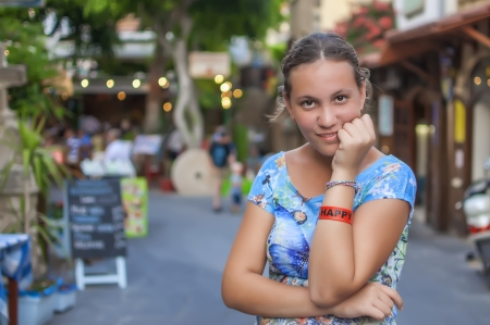 Happy teen girl with bracelet on her arm photo