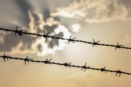 Barbed wire on the background of clouds and sun photo