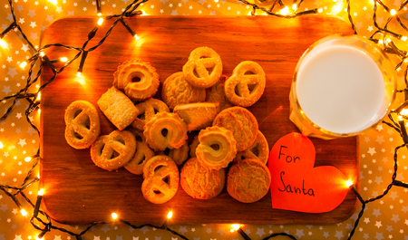 Christmas lights surrounding wooden board with cookies, glass of milk and paper heart For Santa