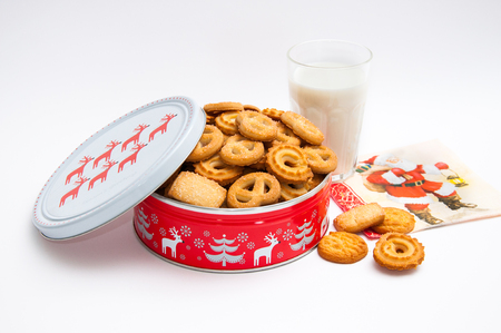Glass of milk and metal box with Christmas cookies