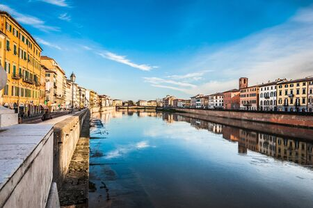 Pisa, Italy - Dec 29, 2017 - Beautiful reflections in the water of river in Pisa, with blue sky on the background