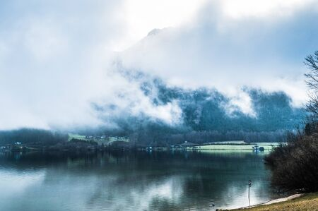 Early foggy  wet morning on the lake between the mountains in Austrian Alps Banco de Imagens