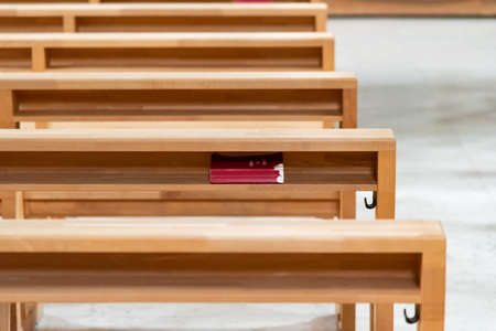Red hymnbook under the prayer kneeling table in the church Banque d'images - 150622877