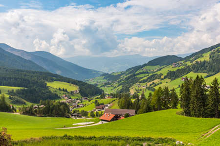 Peaceful Alpine valley with small rural houses and forest on the background