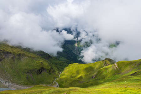 Green mountain under the clouds in Alps