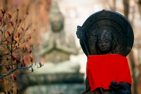 Two buddha statues with red towel photo