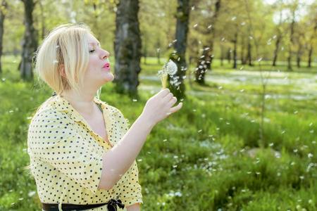 woman blowing: Woman blowing a dandelion Stock Photo