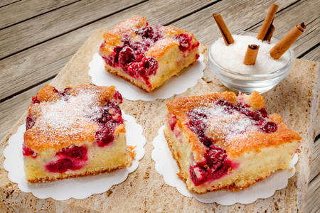 sour cherry: Sour cherry cake. Slices of sour cherry cake with sugar and cinnamon sticks. Stock Photo