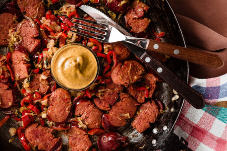 dishcloth: Sliced sausage and mix of fresh vegetables fried in the rustic pan with mustard on dishcloth. Stock Photo