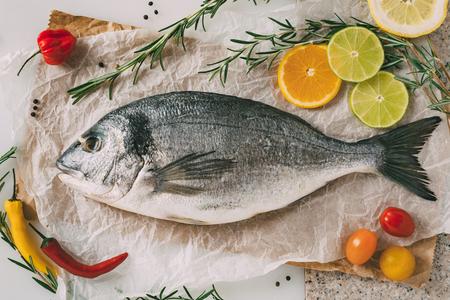 gilthead bream: Sea gilt-head bream fish on baking sheet with rosemary, lemon, orange, tomato, hot peppers and lime. Fresh Orata, Dorade fish on kitchen table. Stock Photo