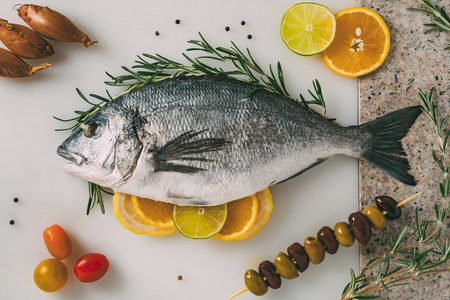 gilthead bream: Sea gilt-head bream fish on kitchen table with rosemary, lemon, orange, olives, tomatoes, onion and lime. Fresh Orata, Dorade fish preparation.
