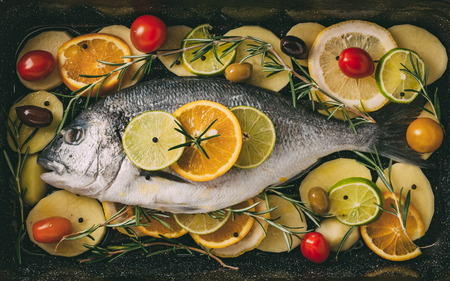 gilthead: Sea gilt-head bream fish in the baking tray ready to be baked with potatoes, rosemary, lemon, orange, olives, tomatoes, onion and lime. Fresh Orata, Dorade fish preparation.