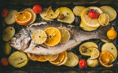 gilthead bream: Sea gilt-head bream fish in the baking tray baked with potatoes, rosemary, lemon, orange, olives, tomatoes, onion and lime. Fresh Orata, Dorade fish preparation. Stock Photo