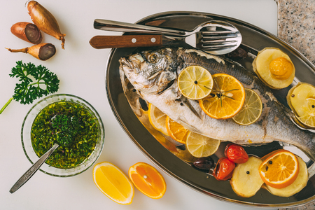 gilthead: Sea gilt-head bream fish on the plate baked with potatoes, rosemary, lemon, orange, olives, tomatoes and lime. Fresh Orata, Dorade fish preparation.