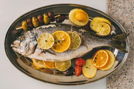 gilthead bream: Sea gilt-head bream fish on the plate baked with potatoes, rosemary, lemon, orange, olives, tomatoes and lime. Fresh Orata, Dorade fish preparation.
