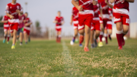 Young football players run in red and white shirts