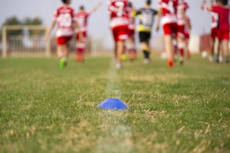 Młodzi piłkarze biegają w czerwono-białych koszulkach