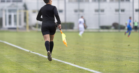 Female assistant refere in action during football