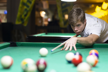 Handsome young man playing pool in pub