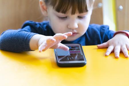 little child girl play on smartphone at home Standard-Bild - 122299387