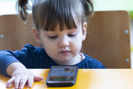 little child girl play on smartphone at home Standard-Bild - 122299389