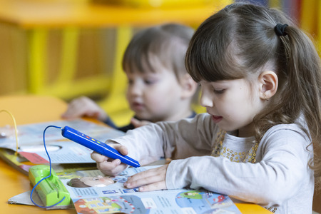 Little girls having fun at school and drawing with colors in kindergarten Reklamní fotografie
