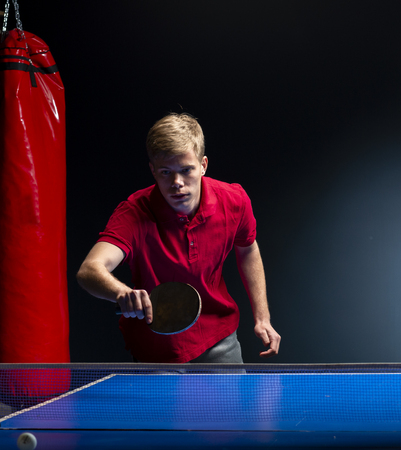 Portrait of young man playing tennis on black background
