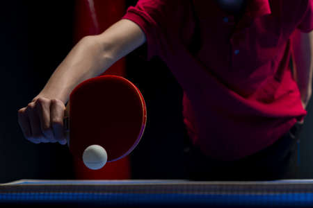 Table tennis ping pong paddles and white ball on blue board